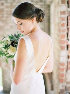 Modern silhouette v-back wedding dress: http://www.stylemepretty.com/2015/11/24/elegant-fall-wedding-in-an-old-textile-factory/   Photography: Kate Ignatoskwi - http://www.kateignatowski.com/