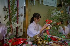 Fukumusume (福娘), or lucky maid, preparing the bamboo grass branches with lucky charms during the annual Toka Ebisu Matsuri in Kyoto.