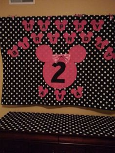 Minnie Mouse birthday banner.  Fabric from Joanne's and cut out the Minnie Mouse silhouettes free hand.  The letters and number two is just black fabric cut out and ironed on with steam a seam lite.  Made the bow from left over fabric from our Minnie Mouse pillows.
