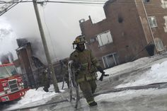 A fireman holds a frozen water hose as he walks away from an apartment building after it was destroyed by a four-alarm blaze on Detroit's west side early March 5, 2014. REUTERS/Joshua Lott