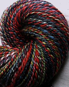 Handspun 2-ply yarn. Black, red, and gold.