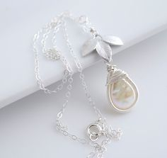 """This beautiful pearl necklace features a pendant made with a ~10x16mm freshwater pearl that has been wire wrapped to create a bezel, a silver leaf and a swarovski crystal. I it hangs from a delicate silv16"""" (40.642cm) sterling silver chain chain."""