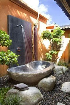 outdoor shower & tub w/ river rocks, boulders & plants  galore! lovely