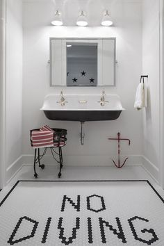 """Fun tile work in a kids bathroom showcasing black and white hexagon floor tiles spelling out """"No DIVING""""."""