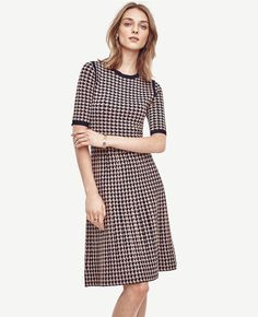 """In timeless houndstooth, this soft and stretchy knit effortlessly refines. Jewel neck. Short sleeves. Ribbed neckline and cuffs. 42"""" from shoulder to hem."""