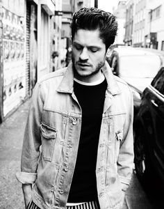 Iwan Rheon captured in a black & white photo, wearing a Tiger of Sweden denim jacket with a Sunspel top and Tomorrowland striped trousers.
