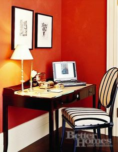 bhg - warm spice colored walls, b&w striped upholestered chair, wide baseboard, b&w prints
