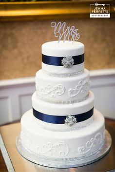 Jazz up a white wedding cake with bling and ribbon that matches your colors at your wedding. Add a cute and classy wedding topper and done!