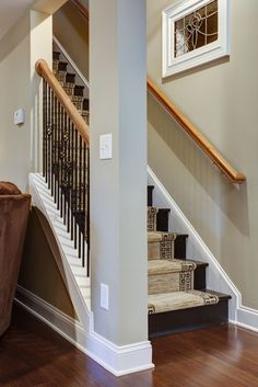 DIY inexpensive stairs in basement. These stairs are painted and distressed with a carpet runner. An opening with metal balusters at these stairs really opened up the entrance of this basement!