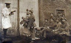This curious German real photograph card is postmarked 1917 and captioned: Wedding on the Western Front. It portrays a mock wedding on the part of soldiers. A makeshift minister performs the ceremony for a soldier-groom in spiked helmet and his cross-dressed male bride, who has donned a dress and is holding what appears to be a bouquet composed of large vegetable leaves. Six fellow soldiers serve as guests.