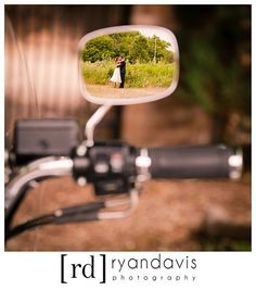 Bride and groom in the mirror of their Harley Davidson motorcycle after a wedding.