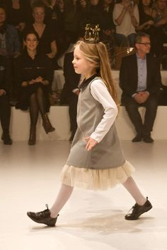 The Crown Princess of Denmark Mary looks on as a young model wears a fairytale crown at CIFF Kids fashion show for winter 2013 kidswear