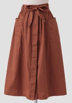 We adore this darling rust-brown colored midi skirt crafted in soft cotton and featuring two front pockets. Finished with a removable sash at the waist and hidden front button closures, this skir...
