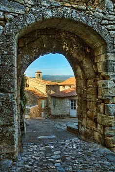 Stone Archway in the Village of Lacoste, Luberon, Provence-Alpes-Cote d'Azur_ France. De mountain seen in de far background is Mont Ventoux