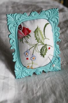 Framed pincushion. I have a few of my great grandmother's old embroidered items, maybe I could try this with some of them.