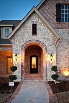 love the color of brick and stone.  Love the pointed tall entryway but i'd want double doors.  Audubon - traditional - exterior - dallas - Joseph Paul Homes