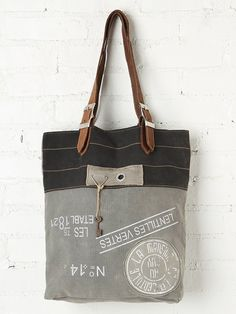 Washed Fielder Tote | Graphic printed, distressed wash canvas tote bag with distressed leather handles. Adjustable buckles at the bottom of each handle where they meet the top of the bag. Inside is fully lined with striped material and has one pocket pouch.