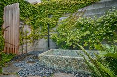 The outdoor bathing area features an outdoor shower, a hot tub and a cold soaking tub. Both tubs are made of embedded river rock that provides a natural foot massage and blends nicely into the garden.