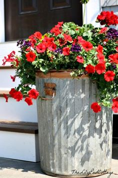 An old galvanized garbage can is used as a simple and inexpensive planter. This can was upgraded by adding copper spray paint to the handles and rim. The Lily Pad Cottage.