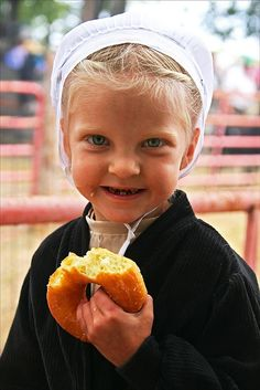 Little Amish Girl Enjoying a Donut