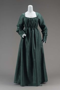Dress c1795-98 American Dimensions 56 11/16 x 14 3/16 in Accession Number 51.1968 Medium or Technique Silk with linen underbodice, and silk drawstring Dress of dark blue-green silk; low square-cut neck, fullness of bodice in front, gathered with a drawstring at neck and at waist; fullness of skirt in back in pleats; long sleeves; linen underbodice. For back, see other pin