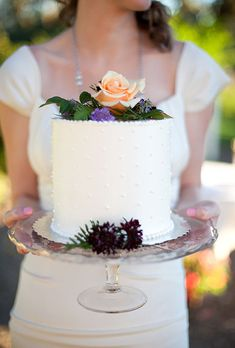 Brides.com: . A one-tier white wedding cake with dotted buttercream details and topped with fresh flowers, created by Crisp Bakeshop.
