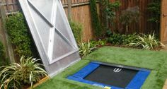 Small garden in Dulwich with a bespoke cover over the sunken trampoline thus making the lawn usable when the trampoline is hidden