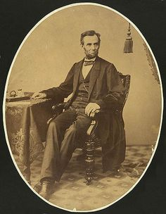 Gardner, Alexander, 1821-1882, photographer. Abraham Lincoln, Sunday, November 8, 1863 [Washington D.C., 1863] 1 photographic print : albumen ; oval 16 1/2 x 12 3/4 in. Notes: Photograph shows President Abraham Lincoln, little more than a week before he gave the Gettysburg Address. Full-length portrait, seated with right arm resting on table, facing slightly right. Published in: Lincoln's photographs: a complete album / by Lloyd Ostendorf. Dayton, OH: Rockywood Press,...