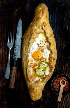 Adjaruli (Acharuli) Khachapuri is a traditional Georgian (the country, that is), canoe-shaped bread filled with a generous amount of cheese and topped with an egg. If you like cheese (and who doesn…