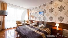 Interior of an elegant hotel room with brown wallpaper, double bed and lit bedside lamps.