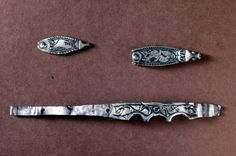 Silver, leaf-shaped strap-end with a single rivet in the split end and a schematic animal-head terminal: beaded sides frame a speckled creat...