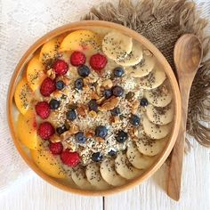 Banana, vanilla and coconut smoothie bowl topped with nectarine, raspberries, blueberries, banana, coconut, chia seeds and crushed walnuts.