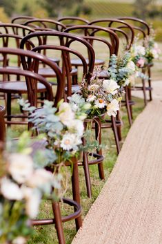 Like these wooden chairs with a little clump of flowers along the aisle. Simple but more special for a back-yard wedding.
