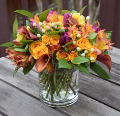 Flower arrangement with oranges, yellows and purples, touch of white hypericum.