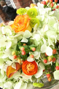 Orange and green wedding centerpiece peach roses, orange ranunculus, coral hypericum berry, green and cream hydrangea.