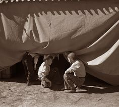 A couple of kids trying to sneak into the Circus under the tent in 1936, NM