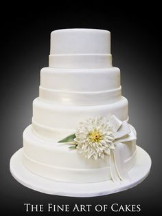 An elegant all white tiered cake featuring a large, detailed sugar delilah flower and ribbon.  Simple, chic and 100% edible.
