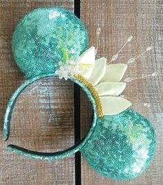 Inspired by the beautiful Tiana these ears are handmade/individually made to order with pale green sequin fabric, gold trim, handcrafted satin crown and beaded embellishments. Each piece is handmade and subtle differences should be expected