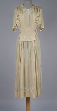 Date Made: 1920s  Description:  Dress; cream silk crepe with white beaded decorative accents on bib, sleeves, and hem. U neckline with pointed V-shaped sailor collar in center back.