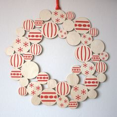 21 Modern Wreaths To Decorate Your Home With This Holiday Season // This wooden wreath with festive screen-printed baubles on it would be great in any mid century modern home.