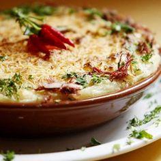 Receita de Escondidinho de Mandioca com Carne de Sol - 300 g de mandioca, 2 colheres (sopa) de azeite de oliva, 2 dentes de alho, 1 tablete de caldo de legu...