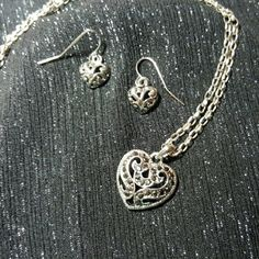 Silver Matching Heart Necklace and Earrings NWOT filgree necklace and earrings set. Heart-shaped silvertone pendant is 1 inch tall from bottom to top of bail and is set with black faceted stones. The 1/2-inch heart-shaped silvertone earrings dangle from silver sheppard hook wires. The sterling siver chain has a lobster claw clasp and is 18 inches in length. Only the chain is sterling silver. All will come in a silk pouch. No trades. Jewelry Necklaces