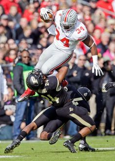 Ohio State running back Carlos Hyde, top, leaps over Purdue defensive back Frankie Williams, left, and safety Taylor Richards (4). (Michael Conroy/AP)