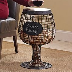 The memories of great bottles shared with close friends tend to be hard to part with. Keep those cherished memories close at hand with our latest wine cork accent table. This innovative wine glass inspired table is made from handcrafted metal with a hinged wooden top. Chalkboard plaque easily wipes clean. Holds approximately 400 corks