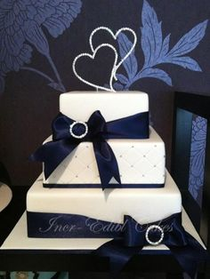 Square wedding cake with diamante hearts and bows with diamante buckles.
