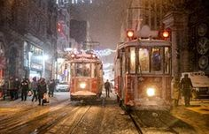 People walk along Istiklal street in Istanbul during snowfall, January 2017