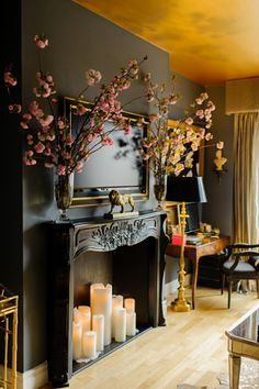 Candles in fireplace! I love the clever use of candles and a fake mantle to give the illusion of a fireplace. Beautiful wall color too. Candles In Fireplace, Black Fireplace, Fireplace Facade, Pillar Candles, Fireplace Wall, Fireplace Modern, Diy Faux Fireplace, Fireplace Design, Simple Fireplace