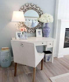 Lamp + mirror + fresh flowers + cushioned chair + pictures + simple desk = such a relaxing work environment!