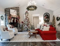 How festive and bright is this Living room all ready for the holiday season? Bright red couch cover, red themed flocked Christmas tree, mantle decor with stockings and greenery around the rustic farmhouse chandelier. Flocked Christmas Trees, Christmas Greenery, Farmhouse Christmas Decor, Christmas Tree Themes, Christmas Mantels, Christmas Home, Farmhouse Decor, Farmhouse Chandelier, Holiday Decor
