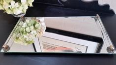 Large vanity mirror with two glass handles measuring approximately 16 long and 9 wide. The mirror has four metal feet on the bottom but one of